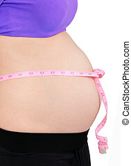 Pregnant woman with pink tape measure on her belly. Isolated...