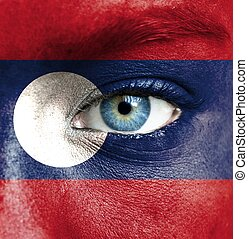 Human face painted with flag of Laos