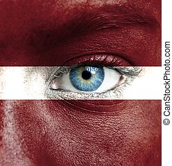 Human face painted with flag of Latvia