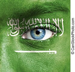 Human face painted with flag of Saudi Arabia