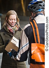 Young Woman Receiving A Package From Courier Delivery Man -...