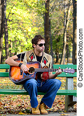 Man playing guitar on bench in park