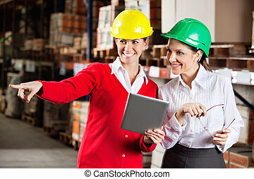 Female Supervisor With Colleague At Warehouse - Happy female...