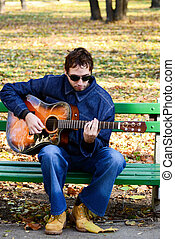 Man playing guitar on bench