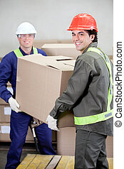 Foremen Lifting Cardboard Box in Warehouse - Portrait of two...