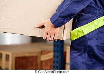 Foreman Carrying Cardboard Box At Warehouse - Midsection of...