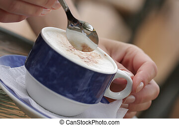 Capuchino - Woman hands holding spoon over cup with...