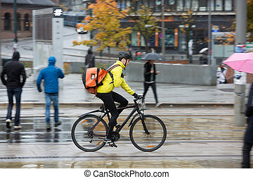Male Cyclist With Backpack On Street - Side view of young...