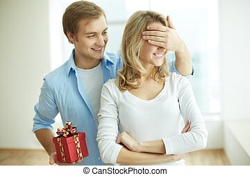 Surprise - Image of young guy with giftbox closing his...