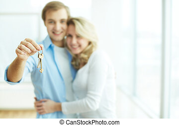 Key to new flat - Image of young happy couple embracing...