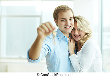 Happy settlers - Image of young happy couple embracing while...