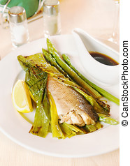 Grilled fish with asparagus on the plate