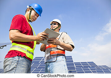 two workers discussing with tablet pc before solar power...