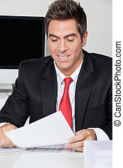 Businessman Reading Document In Office - Happy young...