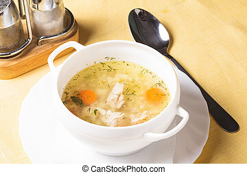 Chicken broth - A chicken broth in white ware on the yellow...