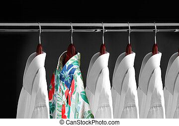 Tropical shirt between white shirts hanging inside a closet