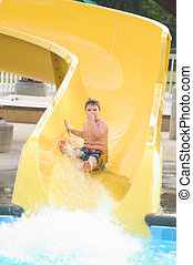 Boy at a Water Park - A young boy sliding down a water...