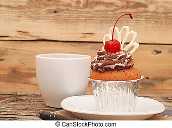 Cupcake with chocolate cream and cherry on old wooden...