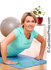 slim mid aged woman do fitness exercises at home
