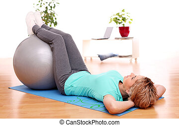 slim mid aged woman do exercises with ball - slim mid aged...