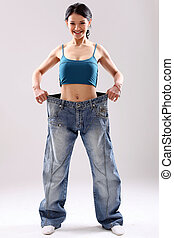 Cute slim girl wearing old jeans after weight loss, in...