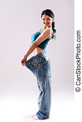 Cute slim girl wearing old jeans after weight loss in studio
