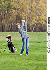 Young golfer swing - Young golfer playing a shot from the...