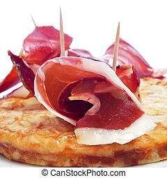 spanish tortilla de patatas and serrano ham - closeup of a...