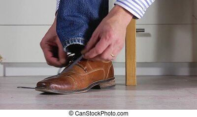 Tying Shoe laces - Close up of a man wearing jeans tying the...