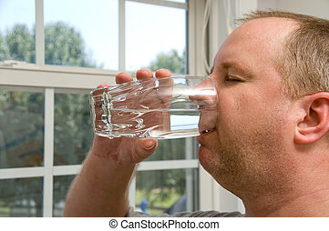 Drinking Water - A man drinking a glass of water.