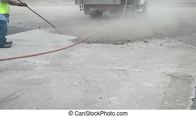 Blowing Dirt to Clean - Worker blows dirt with high...