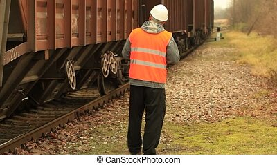 Engineer with phone near the wagons