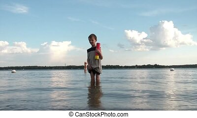 Boy in Lake Squirts Water with Toy - Young boy in a lake...