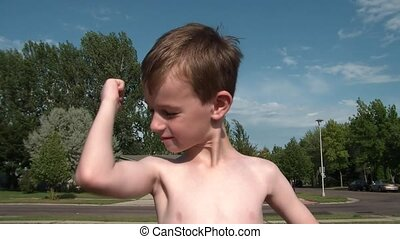 Boy Kisses Muscles in Sun - Young boy kisses his muscles,...