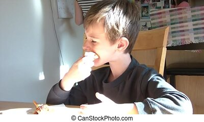Boy Eats Sandwhich at Table - Boy eats a sandwich at a...