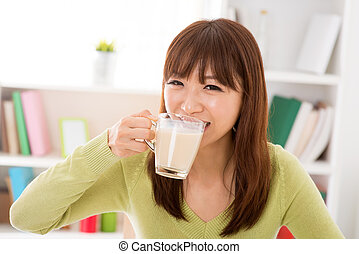 Drinking soy milk - Young Asian woman drinking a glass of...
