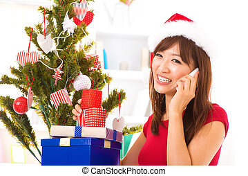 Christmas greeting - Girl in santa hat call mobile phone...