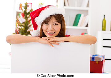 Christmas woman leaning over billboard sign - Asian...