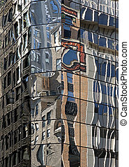 Glass facade with reflection of buildings on opposite street