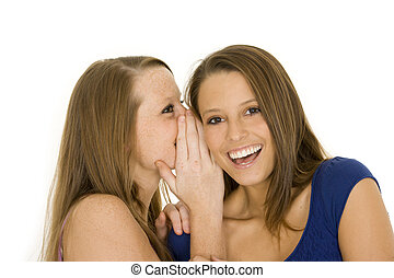 Friends - Two beautiful caucasian women telling secret on a...