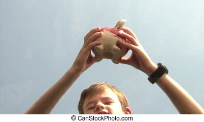 Boy Shaking Piggy Bank - Boy shaking piggy bank while coins...