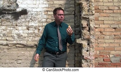 Businessman Eating Fruit Downtown - Businessman eats an...