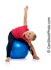 Little girl doing fitness exercise with gym ball. Studio...