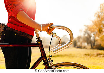 Woman cycling on bicycle in autumn park - Woman cycling on...