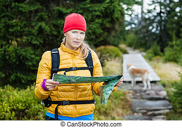Woman hiking and reading map in forest, hiker with dog,...