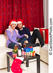 Happy Christmas couple home - Happy Christmas couple sitting...