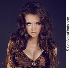 Beautiful woman with brown curly hair and evening make-up...
