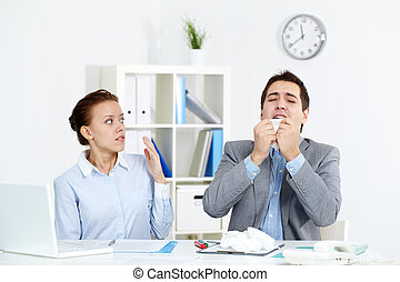 Illness - Image of businessman sneezing while his partner...