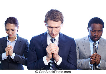 Pray for good result - Three business partners praying with...