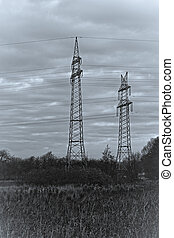Pylons in a natural landscape - black and white with a blue...